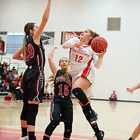 Pine Hill Warriors Maurie Daniels (12) drives to the basket with two Cliff Cowgirls defenders Giovanni Pino (20) and Pauline Martinez (15) in her path during the NMAA State Tournament. The Cowgirls defeated the Warriors 51-40 at Bernalillo High School in Bernalillo Wednesday morning.