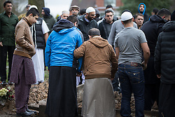 © Licensed to London News Pictures . 03/03/2016 . Manchester , UK . Shahzaib's father JAVID HUSSAIN (in brown jacket) watches as Shahzaib Hussain is buried at Ashton Hurst Cemetary . Shahzaib was killed by a hit and run driver outside the mosque , on Monday 29th February 2016 . Photo credit : Joel Goodman/LNP
