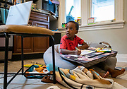 Ethan Gates, 5, practices his letters while participating in his live kindergarten class remotely Thursday, Oct. 22, 2020 in the kitchen of his Chicago home. (Brian Cassella/Chicago Tribune)