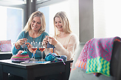 Two women knitting muffler and drinking wine in coffee shop and smiling, Bavaria, Germany
