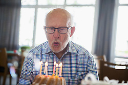 Senior man blowing out birthday candles at rest home, Bavaria, Germany, Europe