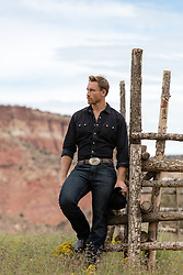 All American handsome cowboy on a rustic ranch overlooking a mountain
