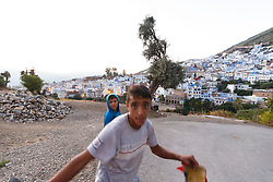 Kids playing  below view of Chefchaouen and the Rif Mountains, Morocco