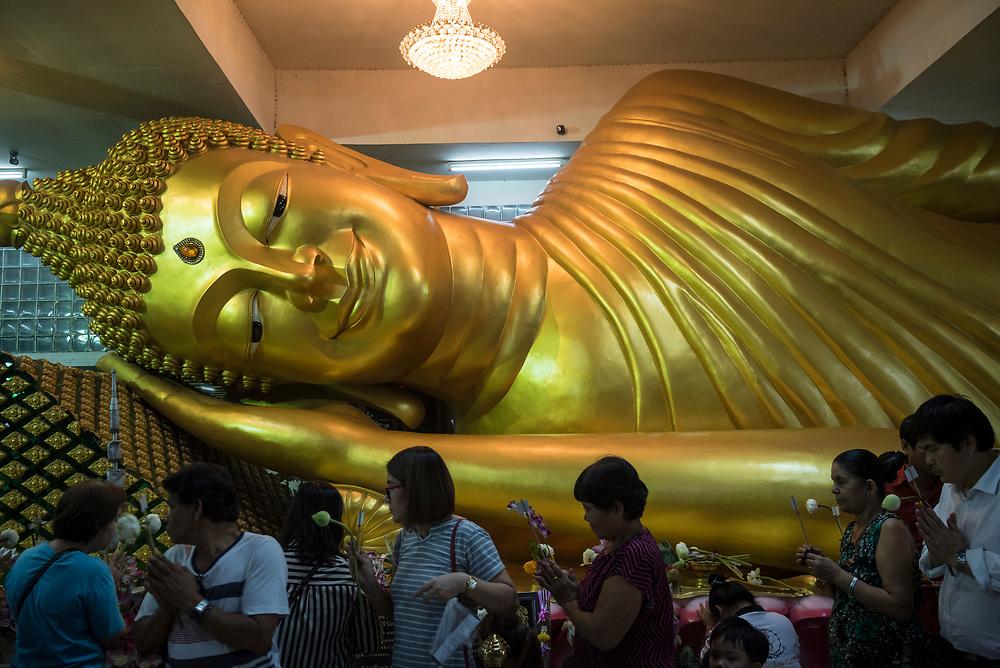 Thai people carrying flowers, including lotus flowers, walk past a reclining Buddha statue at Wat Vorachanyawas Pier in Bangkok, Thailand. (November 2017)