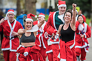Selfie sticks and head cams are out nearing the finish - The London Santa Run 2015 in Battersea Park - 2,000 Santa's take part in an annual 'Red & White' bearded 'charge' around Battersea Park in a 6k festive charity fun run. The runners are of all ages and abilities and many run at a very slow pace but enjoy the event and the cause. The Santa Run is organised to raise funds for Disability Snowsport UK, a national charity helping people with disabilities to access the thrill of snowsports. The charity ensures that children and adults, with a range of disabilities (including cerebral palsy, Down's syndrome,  visual impairment and autism), can access programs across the UK to enable them to make friends, improve their confidence and have fun through a sport which they would otherwise be excluded from.