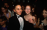 13 year-old Adam leader celebrates his Bar Mitzvah by holding a lavish party in Borehamwood in north London, England. Paid for by his parents, the celebration took place in a hotel off the A1 road and here Adam can be seen surrounded like a celebrity by a gaggle of teenage girl friends, one of whom is dressed in a thin-strapped dress and pendant, giggling at a joke and all enjoying the occasion. Adam looks dashing in a rented dinner jacket complete with bow-tie. He is fresh-faced and clean-cut, cutting a handsome figure much-admired by his female friends.