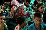 A mother is drying her sweat while sitting with her son on the floor of Chingari Trust Rehabilitation Centre, a local organisation caring for disabled children in Bhopal, Madhya Pradesh, India, near the abandoned Union Carbide (now DOW Chemical) industrial complex, site of the infamous 1984 gas tragedy. The poisonous cloud that enveloped Bhopal left everlasting consequences that today continue to consume people's lives.