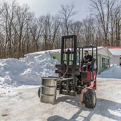 Moving and tracking syrup barrels at the LaRiviere sugarhouse in Big Six Township, Maine.
