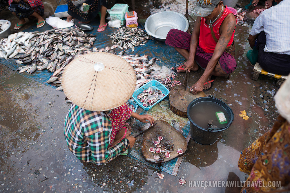 Vendors clean and prepare fish at the fish and flower market in Mandalay, Myanmar (Burma).