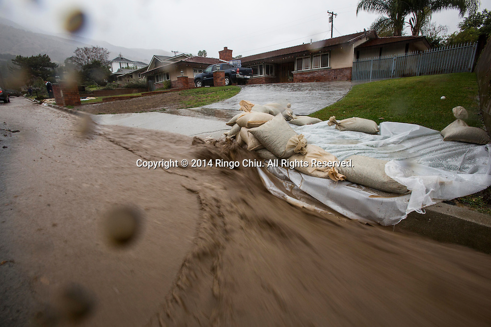 Mud and debris flowing down along a street from the burnt areas in Glendora, California, Tuesday, December 2, 2014. The rain, along with gusty winds, is the result of a Pacific storm system. Forecasters said the storm should drop about 1 to 2 inches of rain along the coast and in valley areas, and 2 to 5 inches in the mountains and foothills.(Photo by Ringo Chiu/PHOTOFORMULA.com)