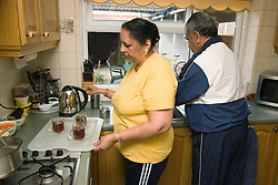Older woman making cups of tea whilst husband is at the sink washing up,