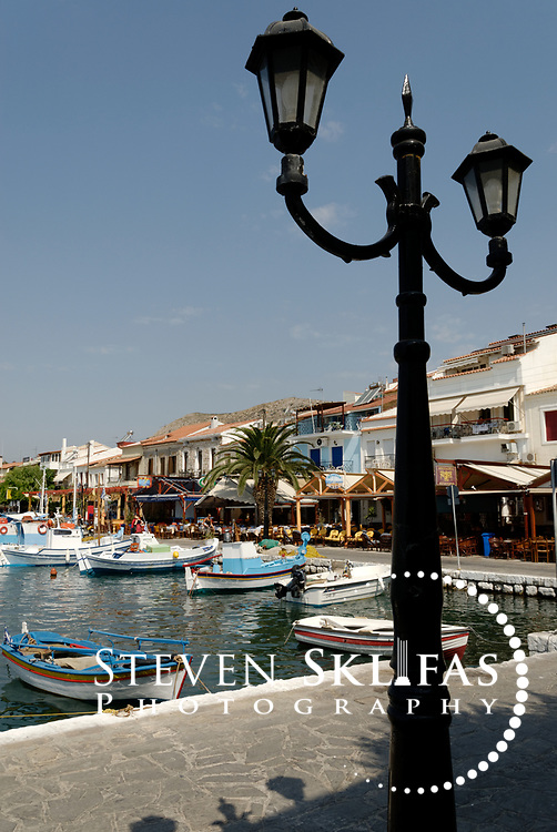 Samos. Greece. View of a lamp post on the Pythagoreio waterfront and colourful fishing boats docked in its pretty harbour. The town of Pythagoreio is the most popular and fashionable town on the island and was named after the great philosopher Pythaogaras who was born here in 580 BC.