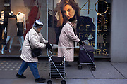 Two elderly ladies push near-identical trolleys past a womens' clothes shop in Chelsea. Helping them walk, they lean on the handles of these shopping accessories as they make their unsteady way along the trendy shopping street in West London. In the window of the fashion store is a large poster of a beautiful model, as if reminding them of their own youth and beauty. We see a scene of ageism and the passing of time, of generations of women starting young lives and passing into old age, needing to be aided with supports.
