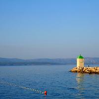 Harbour and bouys at sea with Hvar mountains in the distance; <br />Bol, Brac, Croatia.
