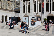 City workers enjoy spring sunshine during their lunch hours at the Guildhall, next to an outdoor photography exhibition on the theme of mental health, in the City of London, the capitals ancient, financial district, on 14th May, in London, England. Located in the courtyard of Guildhall Yard, Let's Talk is a collaboration between photographer Charlie Clift and artist Kate Forrester. It takes the form of a series of large photographs of celebrities.