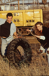 couple at a industrial site pushing a tractor tire