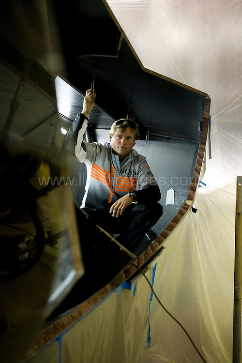 """08.10.23 Alex Thomson's Open 60 """"Hugo Boss"""" pictured here being repaired after being hit by a French fishing trawler whilst waiting to enter the race village in Les Sables D'Olonne. France......All pictures must be credited """"Lloyd Images""""."""