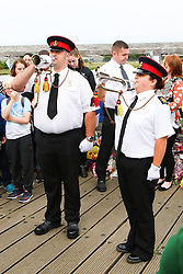 © Licensed to London News Pictures. 29/08/2015. Shoreham, UK. James Williams, 31 and Anita Charania, 32 from the Surrey and Sussex Drum and Bugle Corps play ahead of the minute silence. Thousands of flowers can be seen on the Footbridge where today people holding a minute silence at 1.20pm to remember the 11 confirmed victims of the plane crash of a Hawker Hunter Jet at the Shoreham Airshow on August 22nd, Today August 29th 2015. Photo credit : Hugo Michiels/LNP