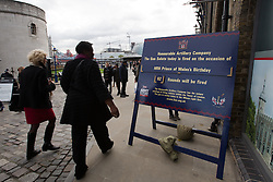 © Licensed to London News Pictures. 14/11/2013. London, UK. People walk past a sign stating that soldiers of the Honourable Artillery Company (HAC) will fire a 62 gun salute at Tower Wharf outside the Tower of London to mark Prince Charles birthday today. Photo credit : Vickie Flores/LNP