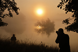 © Licensed to London News Pictures. 22/09/2021. London, UK. People  watch the sunrise over Pen Ponds in Richmond Park on the first day of autumn. Warm temperatures have heralded the start of the autumn season this week. Photo credit: Peter Macdiarmid/LNP