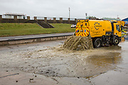 A bright yellow Sweeptech specialised vehicle cleaning out rubbish and silt from the bottom of Hove Lagoon, Kingsway,  Hove, East Sussex, United Kingdom.