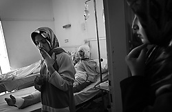 """Alameda Ghaith, a student, stands by her father Mohammed Ghaith's hospital bedside after their home was hit by a rocket from an Israeli helicopter earlier in the week, in Tyre, Lebanon, July 27, 2006. <br /> Her mother and sister, who was set to be married the following month, died instantly. She asked, """"Do we look like Hezbollah fighters to you?"""""""