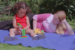 Teenage mother lying on picnic blanket in garden watching young daughter playing with stickle bricks,