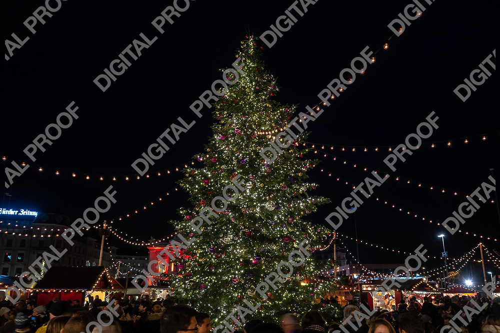 Zurich, Switzerland - December 22, 2018 Natural christmas tree illuminated and surrounded by people at Christmas market held at Sechseläutenplatz