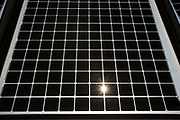 Close-up of a photovoltaic solar energy panel with the sun shining through. This panel, or module, is made up of photovoltaic PV cells. PV cells convert sunlight into electrical energy. Photovoltaic panels are an economical, efficient way to produce electricity that does not pollute or contribute to global warming. London, United Kingdom.