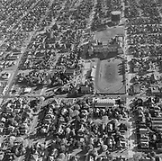 Y-560400A-10.  Piedmont area looking south. Killingsworth St. near center in front of Jefferson High School football field. Public Library & Chapel of the Chimes. Note gas tank behind Jefferson. March 1956.
