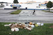 In front of a closed Ecomax supermarket, a cyclist pedals past heap of rubbish lying in colonial Kourou car park