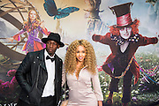 Imani and partner - Alice Through the Looking Glass premiere - a Walt Disney American fantasy adventure film directed by James Bobin, written by Linda Woolverton and produced by Tim Burton. It is based on Through the Looking-Glass by Lewis Carroll and is the sequel to the 2010 film Alice in Wonderland. The film stars Johnny Depp, Anne Hathaway, Mia Wasikowska, Rhys Ifans, Helena Bonham Carter, and Sacha Baron Cohen and features the voices of Alan Rickman, Stephen Fry, Michael Sheen, and Timothy Spall.