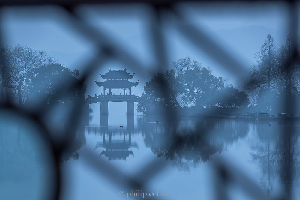 Blue landscape with silhouetted Yudai Bridge, trees and West Lake during dawn, Hangzhou, Zhejiang Province, China