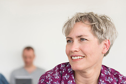 Portrait of mature smiling woman while mature man using digital tablet in the background