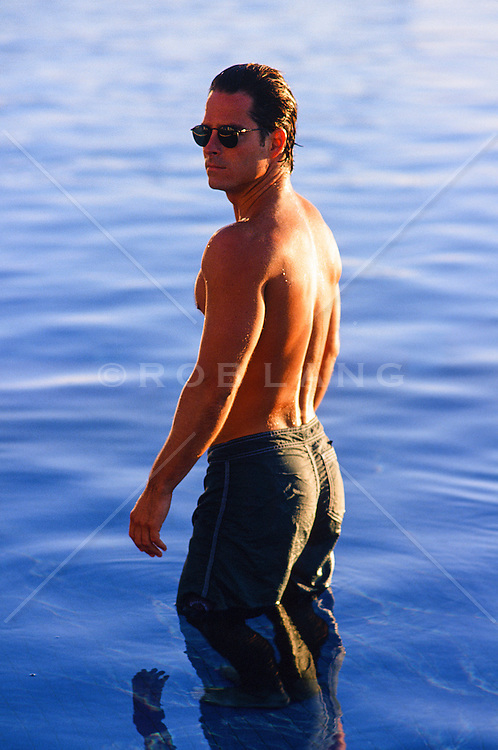handsome man standing in calm water without a shirt and wearing sunglasses