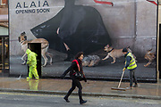 As workmen hose down the muddy pavement, a passer-by carefully walks beneath a large construction hoarding for Alaia on New Bond Street, on 17th January 2018 in Westminster, London, England.