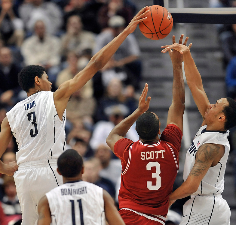 Connecticut's Jeremy Lamb, top left, blocks a shot of Arkansas' Rickey Scott (3), as Shabazz Napier, second from right defends and teammates Ryan Boatright (11) and Alex Oriakhi, right, look on in the first half of an NCAA college basketball game in Hartford, Conn., Saturday, Dec. 3, 2011.  (AP Photo/Jessica Hill)