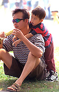Boy hanging on fathers shoulders ages 30 and 5. Cedarfest Summer Music Festival Minneapolis  Minnesota USA