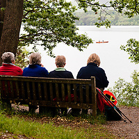 Four senior women enjoys a moment of rest during a hike in the lake district, UK