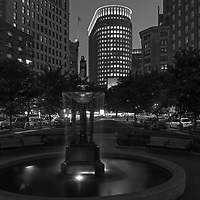Boston skyline B&W photography from New England photographer Juergen Roth showing the Boston Statler Park and parts of its fountain with the Boston Park Plaza to the right. The left features a rental apartment complex. I noticed the fountain and phot opportunity when I picked up my wife from a gala at the Boston Plaza Hotel. The fountain inspired me to come back at twilight and create this long-exposure photography image of the Boston cityscape. <br />