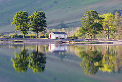 © Licensed to London News Pictures. 07/06/2018. Buttermere UK. Tree's on the banks of Buttermere lake reflect into the still water this morning on a sunny day in Cumbria. Photo credit: Andrew McCaren/LNP