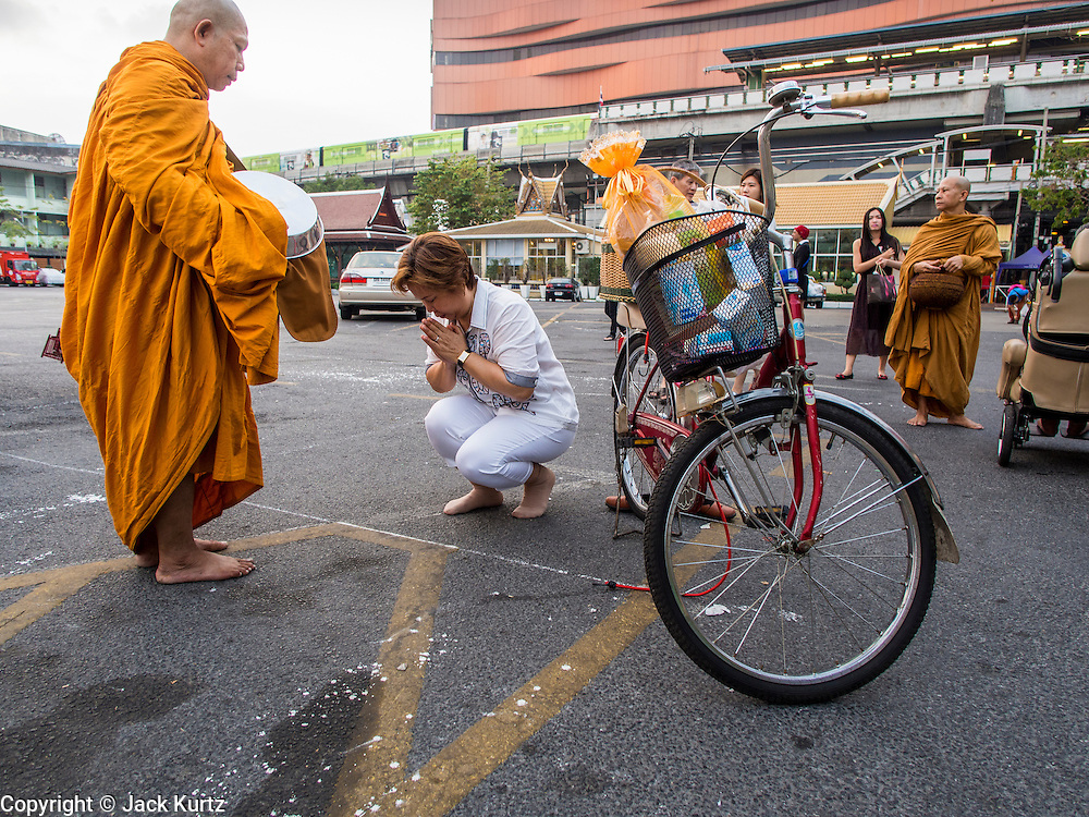 """14 FEBRUARY 2014 - BANGKOK, THAILAND:  A woman presents alms to a monk on Makha Bucha Day at Wat That Thong (also called Wat Tad Tong) in Bangkok. The aims of Makha Bucha Day are: not to commit any kind of sins, do only good and purify one's mind. It is a public holiday in Cambodia, Laos, Myanmar and Thailand. Many people go to the temple to perform merit-making activities on Makha Bucha Day. The day marks four important events in Buddhism, which happened nine months after the Enlightenment of the Buddha in northern India; 1,250 disciples came to see the Buddha that evening without being summoned, all of them were Arhantas, Enlightened Ones, and all were ordained by the Buddha himself. The Buddha gave those Arhantas the principles of Buddhism, called """"The ovadhapatimokha"""". Those principles are:  1) To cease from all evil, 2) To do what is good, 3) To cleanse one's mind. The Buddha delivered an important sermon on that day which laid down the principles of the Buddhist teachings. In Thailand, this teaching has been dubbed the """"Heart of Buddhism.""""   PHOTO BY JACK KURTZ"""