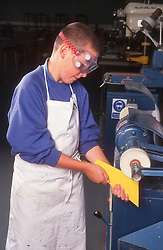 Design and technology student wearing safety goggles using machine to sand piece of plastic,