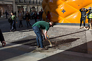 A florist working from a nearby kiosk empties stale water into a drain near the temporary renovation hoarding of luxury brand Louis Vuitton in New Bond Street, on 25th February 2019, in London, England.
