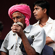 A man thoughtfully sips on his chai as the speeches continue.