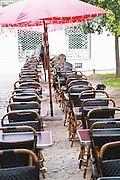 Cafe. Montpellier. Languedoc. A lone person sitting in a long row of chairs at a cafe. France. Europe.