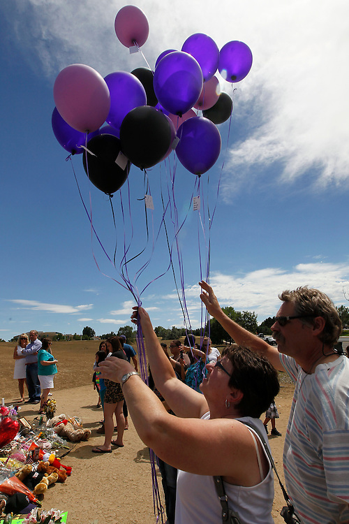 Deann Schmied (L) with her busband Wayne (R) waving at the memorial cross releases balloons in honor of their son's friend A.J.Boik at a memorial in Aurora, Colorado July 28, 2012. Killed in the July 20, 2012 theater shootings the funeral was held yesterday for Boik, an 18-year-old man who had been bound for art college in the fall.  REUTERS/Rick Wilking (UNITED STATES)