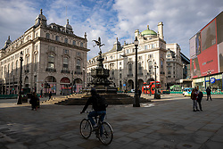 © Licensed to London News Pictures. 09/11/2020. London, UK. A man cycles through a quiet Piccadilly Circus in Central London. A second national lockdown is now in place to slow the spread of Coronavirus and is expected to last until 2 December 2020. Photo credit: Rob Pinney/LNP