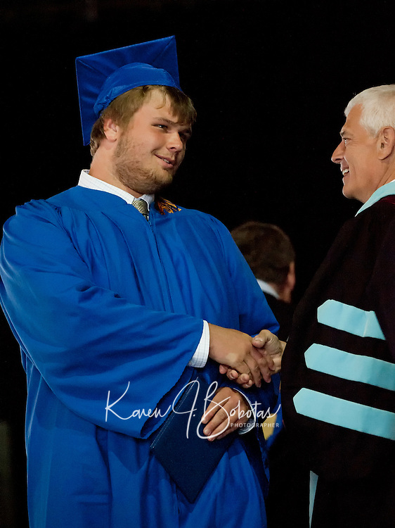 Gilford High School graduate Ryan Carr is congratulated by Dr. Paul DeMinico after receiving his diploma at Meadowbrook Saturday morning.  (Karen Bobotas/for the Laconia Daily Sun)Gilford High School Graduation at Meadowbrook Pavilion Saturday, June 11, 2011.