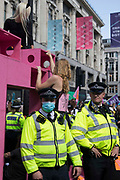 Women and FINT-identifying environmental activists from Extinction Rebellion block Oxford Circus with a large pink structure during the third day of Impossible Rebellion protests on 25th August 2021 in London, United Kingdom. Extinction Rebellion are calling on the UK government to cease all new fossil fuel investment with immediate effect.